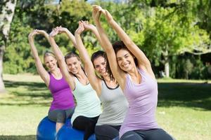 Fitnessgruppe sitzt auf Gymnastikbällen