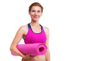 Porträt der jungen schönen Frau, die Yogamatte hält - isoliert. foto