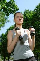 Fitnessfrau, die Übungen mit leichten Hanteln macht foto