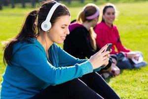 Freunde, die nach dem Training Spaß mit Smartphones haben foto