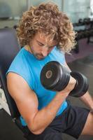 schöner Mann, der mit Hantel im Fitnessstudio trainiert foto