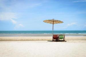 Liegestühle auf dem Sandstrand mit bewölktem blauem Himmelhintergrund
