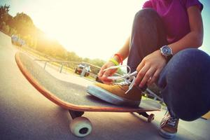 junger asiatischer Skateboarder, der Schnürsenkel auf Skateboard bindet foto