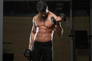 Bodybuilder trainieren Bizeps mit Hanteln