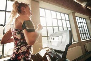 Frau, die auf einem Laufband im Fitnessstudio trainiert foto
