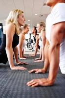 junge Fitnessleute, die Dehnungsübung auf dem Boden tun foto