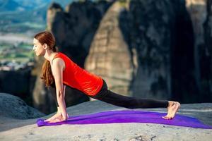 Frau, die Yoga auf den Bergen praktiziert
