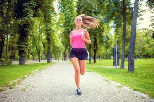 glückliche Frau, die im Stadtpark mit Kopfhörern läuft