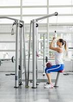 junge Frau, die im Fitnessstudio trainiert foto