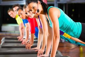 Gruppe von Menschen und Ausbilder im Fitnessstudio Stretching foto