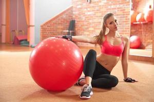 Fitnessfrau, die auf Fitnessball trainiert foto