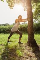 Frau, die sich gegen einen Baum bei Sonnenuntergang streckt foto