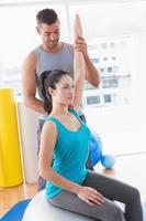 Trainer, der Frau unterstützt, die auf Fitnessball trainiert foto