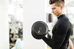 junger hübscher Mann, der in einem Fitnessstudio trainiert