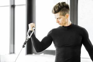 junger Mann, der in einem Fitnessstudio trainiert foto