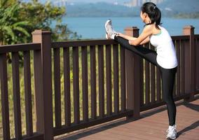 Sportfrau streckt die Beine vor dem Laufen foto