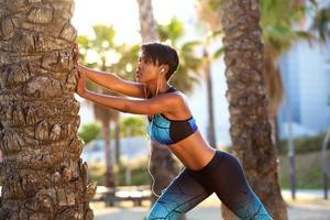 schöne schwarze Frau, die Trainingsroutine streckt foto