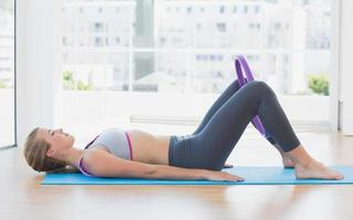 sportliche Frau mit Übungsring im Fitnessstudio