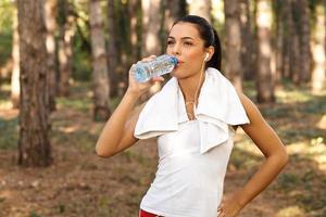 schöne Fitnessfrau Trinkwasser aus Plastikflaschen