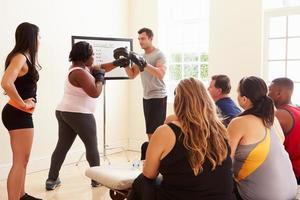 Fitnesstrainer im Übungskurs für übergewichtige Menschen foto