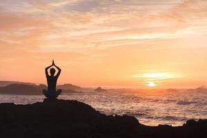 Frau kämpft gegen Stress, indem sie Yoga in der Nähe des Meeres praktiziert