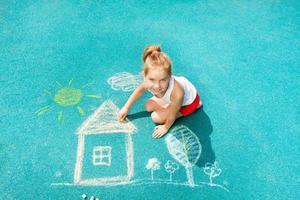 nettes kaukasisches kleines Mädchen zeichnen Kreidehausbild foto
