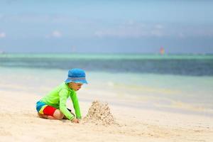 kaukasischer Junge, der Sandburg am tropischen Strand baut foto