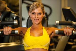 schöne kaukasische Frau, die ihre Arme in der Fitness ausarbeitet foto