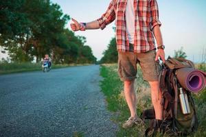 junger kaukasischer Tourist, der entlang einer Straße per Anhalter fährt foto