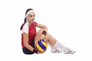 kaukasische professionelle weibliche Volleyballspielerin, die mit Ball sitzt foto