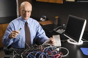 kaukasischer Geschäftsmann in einem Gewirr von Computerkabeln. foto