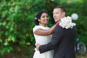schöne indische Braut und kaukasischer Bräutigam im Park foto