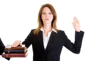 kaukasische Frau, die auf einem Stapel des weißen Hintergrunds der Bibeln schwört foto