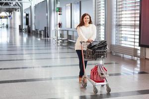 junge kaukasische Frau, die Gepäckwagen in der Flughafenhalle zieht foto