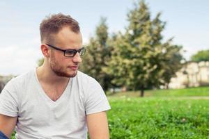 Porträt des bärtigen jungen Mannes. trauriger kaukasischer Mann im Park. foto