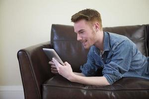 kaukasischer Mann, der digitales Tablett zu Hause auf Sofa verwendet. foto