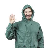 kaukasischer Mann im Regenanzug mit Kapuze, der mit Palme verzichtet.