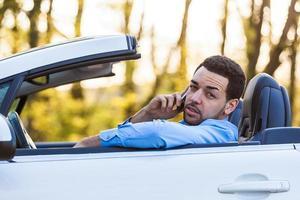 junger lateinamerikanischer Fahrer, der während der Fahrt einen Anruf tätigt