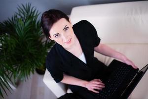 fröhliche junge kaukasische Geschäftsfrau, die mit Laptop-Computer sitzt