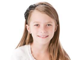 echte Menschen: lächelnde kaukasische kleine Mädchen Bogen durchbohrte Ohren foto