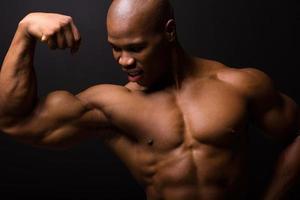 afrikanischer Bodybuilder auf schwarzem Hintergrund foto