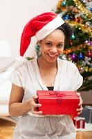 junge Afroamerikanerfrau, die eine Geschenkbox hält foto