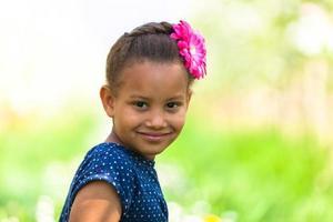 Außenporträt eines niedlichen jungen schwarzen Mädchens lächelnd foto