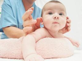 Arzt Massage kleines kaukasisches Baby foto