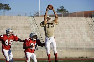 gegnerische amerikanische Fußballspieler, die um Ball konkurrieren foto