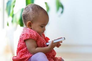 Porträt des kleinen afroamerikanischen kleinen Mädchens, das ein Handy hält foto