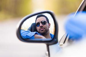 junger schwarzer lateinamerikanischer Fahrer, der sein neues Auto fährt