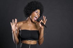 Afroamerikanerfrau, die auf Mikrofon singt foto