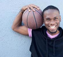 fröhlicher Afroamerikaner, der Basketball hält foto