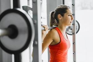 junge schöne Frau, die Gewichte in einem Fitnessstudio hebt